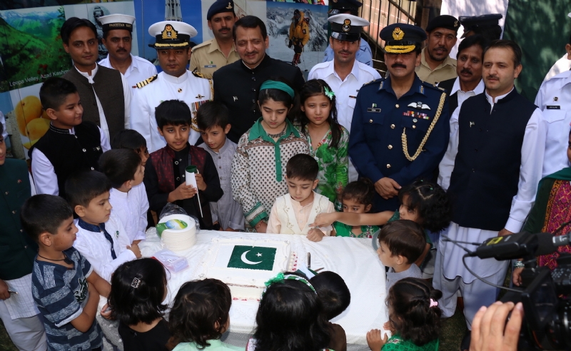 Cdr Syed Ali Asad Gilani cutting cake to mark national day of Pakistan on 14 August 2017