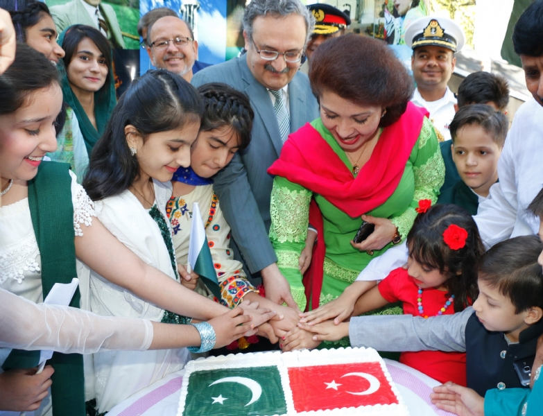 Ambassador Syrus Qazi and his spouse Dr. Shaza Syrus flanked by Pakistani children cutting Independence Day cake